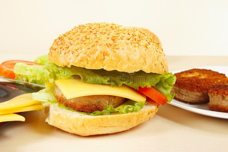 Wielki przyprawiony hamburger z serowym zbliżeniem obrazy royalty free