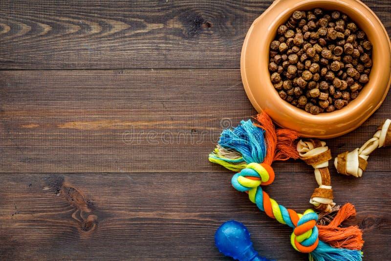 Wielki puchar zwierzę domowe - psi jedzenie z zabawkami na drewnianym tło odgórnego widoku mockup obrazy stock