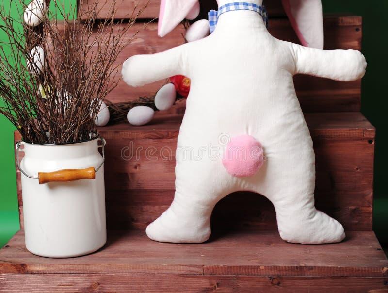 Wielki różowy miękki królik w w kratkę łęku krawacie z Wielkanocną dekoracją Tylni widok, różowy ogon obrazy stock