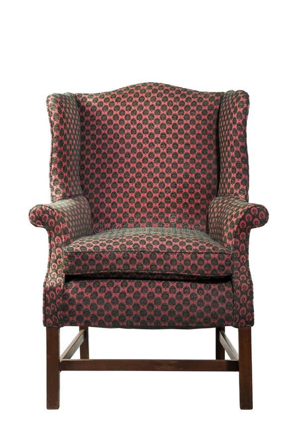 Wielki skrzydłowy krzesło tapicerujący w czerwonym starym antyku odizolowywającym fotografia royalty free