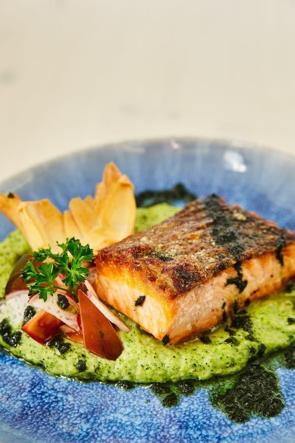 Wielki soczysty piec tłusty kawałek łososiowy stek na poduszce jarzynowy puree, dekorującej z rzodkwią, pietruszka, cilantro i pi fotografia royalty free