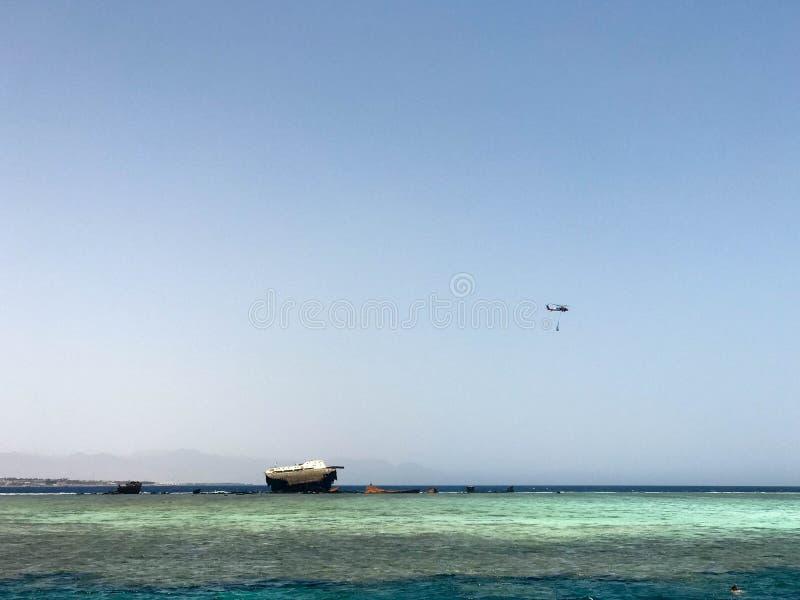Wielki statek, liniowiec, tankowiec łamający po trzaska na rafach koralowa przeciw pięknemu tropikalnemu krajobrazowi b i helikop obrazy royalty free