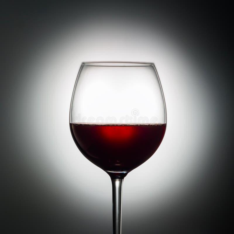 Wielki szklany czerwone wino kształt zmrok od winogrono alkoholicznego napoju na świecącym tło reklamy strzale obraz royalty free