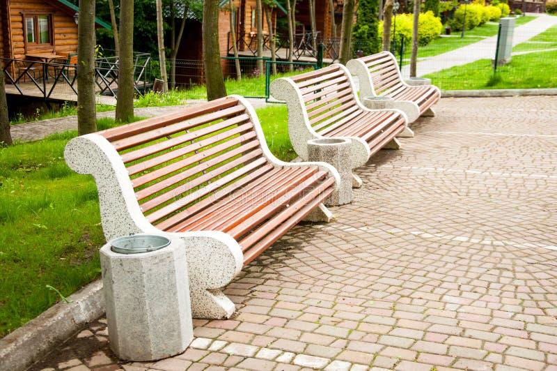 Wielkie betonowe ławki z drewnianymi elementami Blisko alei w parku Lato w jardzie drzewo pola obrazy royalty free