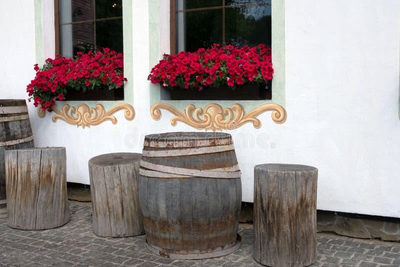 Wielkie drewniane baryłki na białym ściennym tle Czerwone petunie na okno Projekt jard fotografia royalty free
