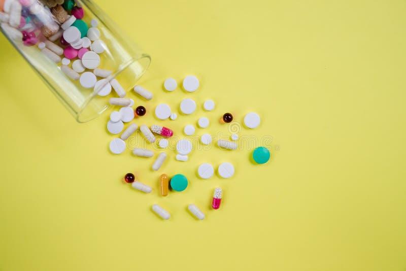 Wielkie i jaskrawe pigułki czerwieni, białych i kolorowych, rozpraszają od szkła odizolowywającego Na żółtym tle medyczny zdjęcie stock