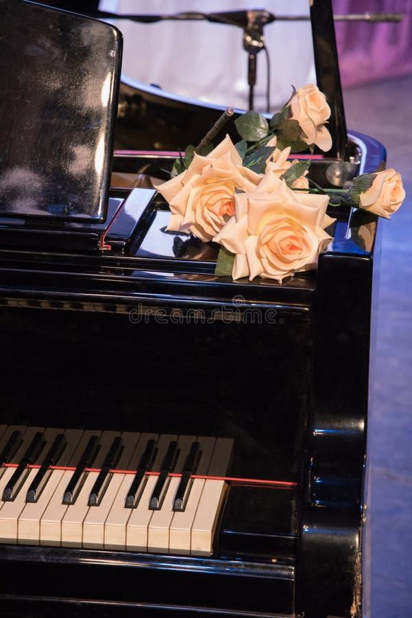Wielkie pomarańczowe róże kłamają na czarnym starym pianinie z kluczami na sta obrazy stock