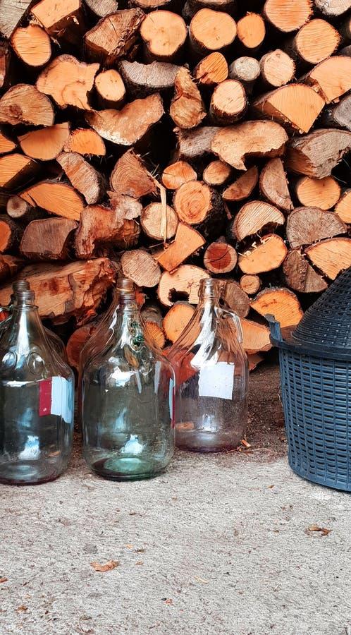 Wielkie szklane butelki i drewno w woodpile zdjęcia royalty free