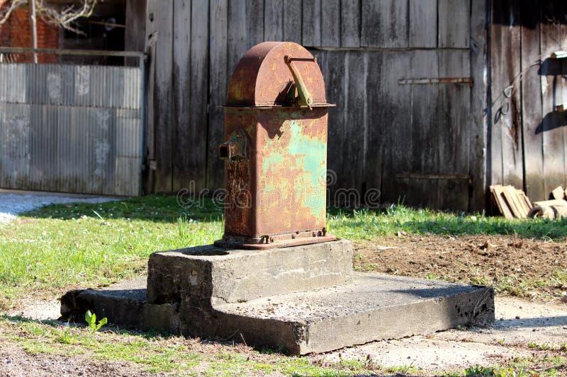 Wielkiego rocznika ręki retro stronniczo rdzewiejąca jawna pompa wodna wspinająca się na obdrapanej betonowej podstawie otaczając fotografia royalty free