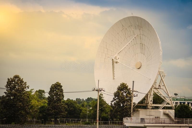 Wielkiej skala biała antena satelitarna w słonecznym gospodarstwie rolnym pod dramatycznym obrazy stock