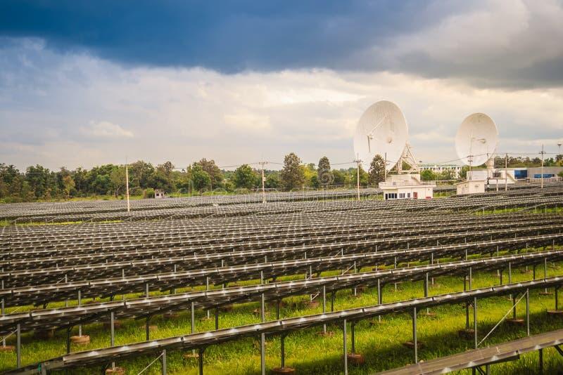 Wielkiej skala słoneczny gospodarstwo rolne z antenami satelitarnymi pod dramatycznym fotografia stock