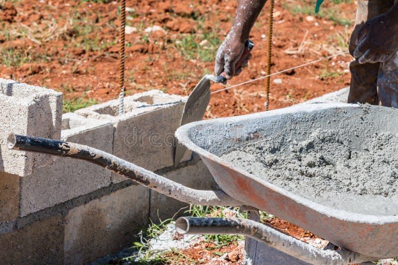 Wielkruiwagen met nat cement naast metselaar/metselaar/bouwvakker wordt gevuld die stock afbeeldingen
