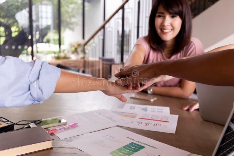 Wielo- etniczne istot ludzkich ręki z twarzą piękny Azjatycki biznesowej kobiety kładzenie wręczają wpólnie w jedności obrazy stock