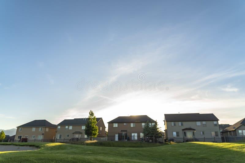 Wielo- kondygnacja stwarza ognisko domowe z białymi ścianami i ogrodzeniami przegapia pole golfowe obraz stock