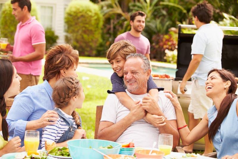 Wielo- pokolenie rodzina Cieszy się posiłek W ogródzie Wpólnie fotografia stock
