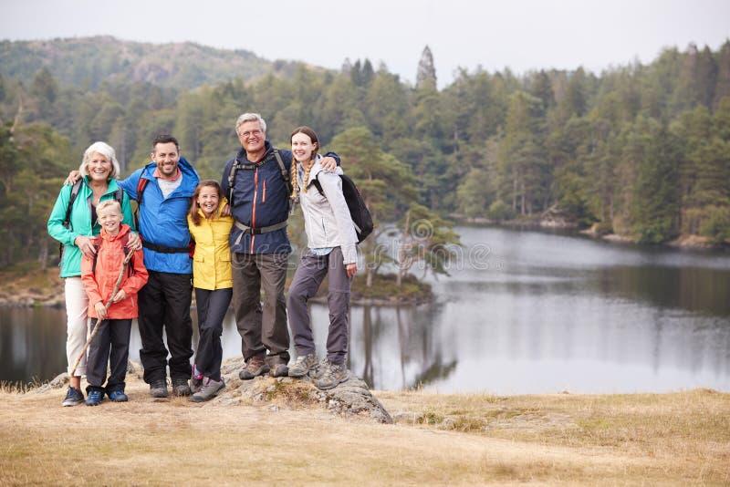Wielo- pokolenie rodziny stojak obejmuje jeziorem, ono uśmiecha się kamera, frontowy widok, Jeziorny okręg, UK obraz stock