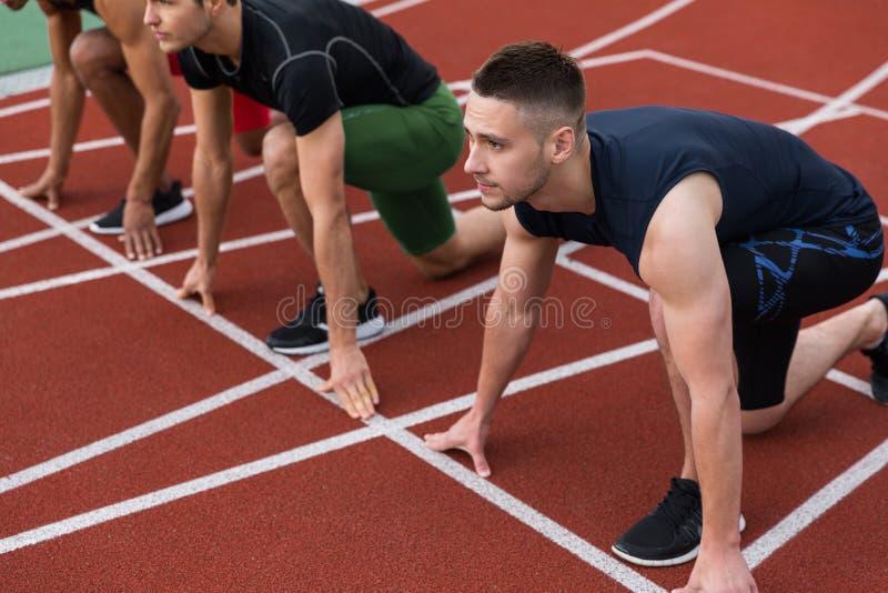 Wieloetniczna atlety grupa przygotowywająca bieg zdjęcie stock