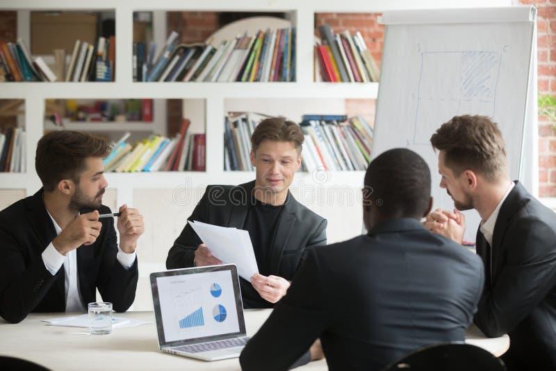 Wieloetniczna drużyna męscy coworkers dyskutuje korporacyjnych plany du obrazy stock