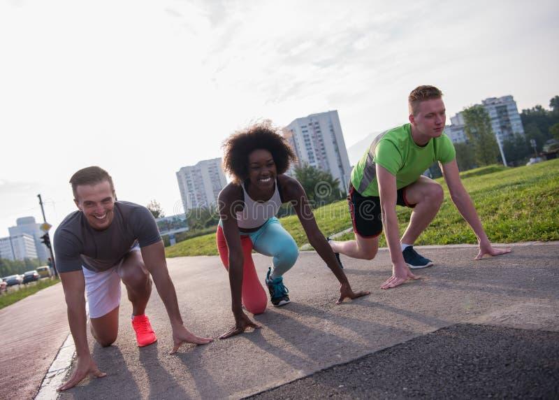 Wieloetniczna grupa ludzi na początek pozyci dla jogging zdjęcie royalty free
