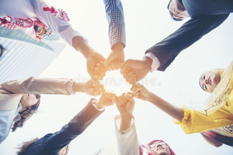 Wieloetniczna grupa młoda pracy zespołowej pozycja wręcza wpólnie prac zespo?owych poj?cia obrazy stock