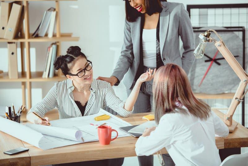 Wieloetniczna grupa młodzi bizneswomany pracuje z projektami i dyskutować zdjęcie stock