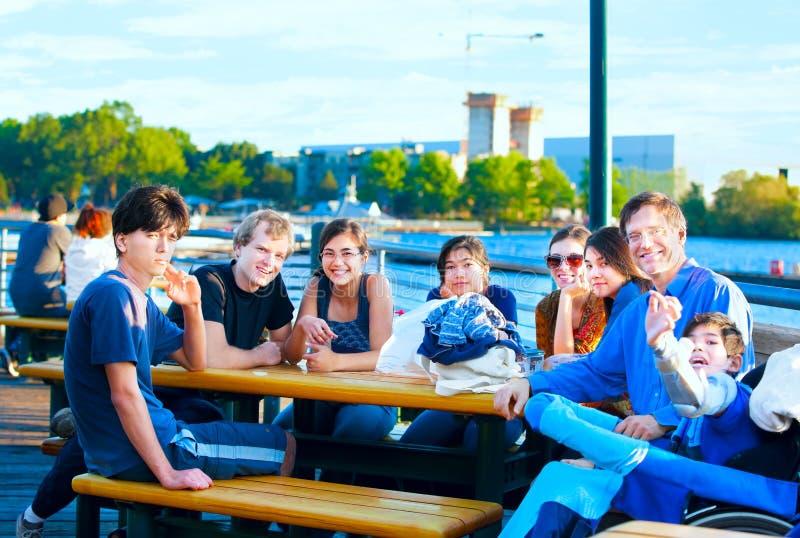 Wieloetniczna grupa młodzi ludzie przy brzeg jeziora parkiem obrazy stock
