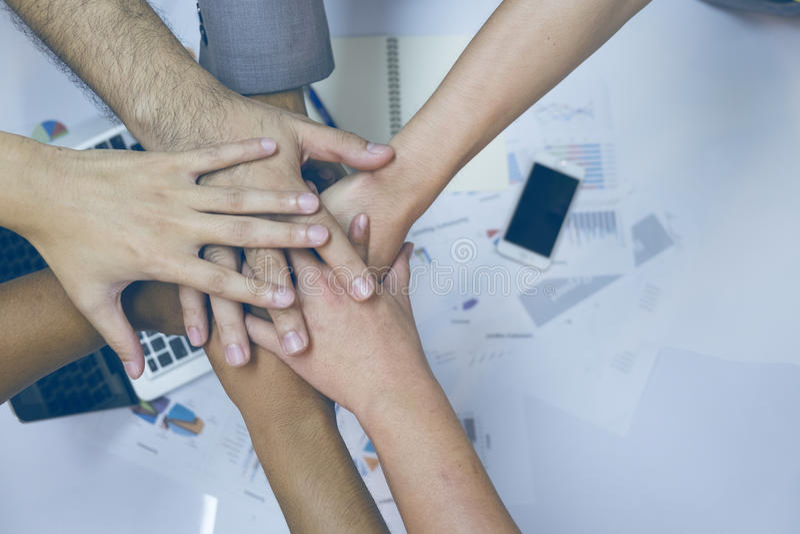 Wieloetniczna grupa młodzi ludzie stawia ich ręki na górze each inny zdjęcia royalty free