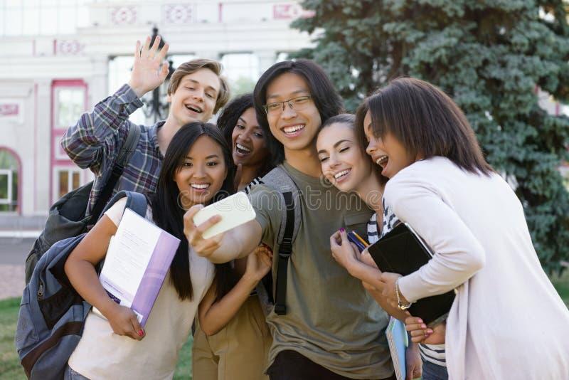 Wieloetniczna grupa młodzi szczęśliwi ucznie robi selfie outdoors zdjęcia stock