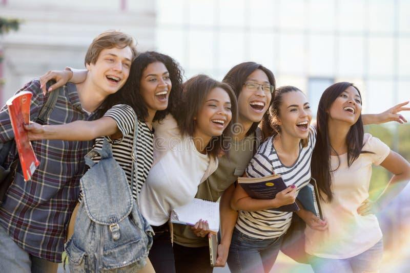 Wieloetniczna grupa młodzi szczęśliwi ucznie stoi outdoors obrazy stock