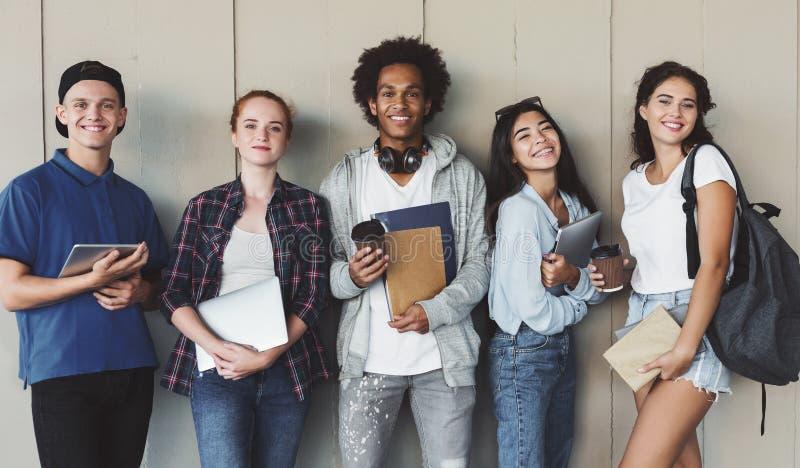Wieloetniczna grupa rozochoceni młodzi ucznie stoi wpólnie zdjęcie royalty free