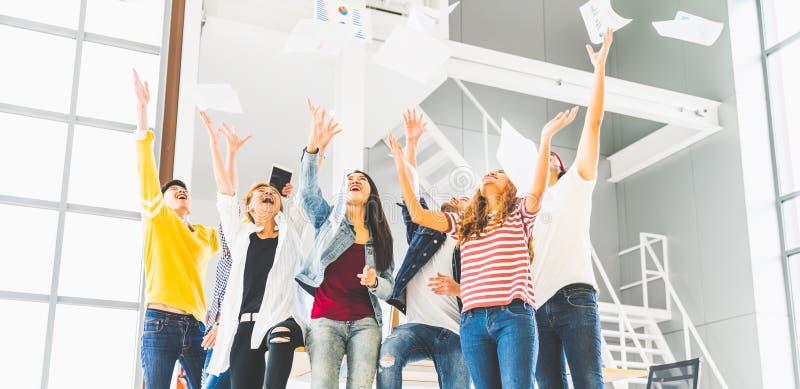 Wieloetniczna różnorodna szczęśliwa drużyna świętuje projekta sukcesu rzutu papier up wpólnie Korporacyjna społeczność lub małego obraz royalty free