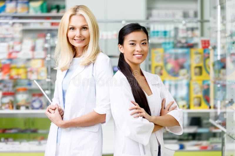 wieloetniczne farmaceuty stoi i ono uśmiecha się przy kamerą w białych żakietach z krzyżować rękami zdjęcie stock