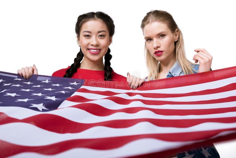 Wieloetniczne kobiety patrzeje kamerę i trzyma flaga odizolowywająca na bielu usa, dnia niepodległości świętowanie obraz stock