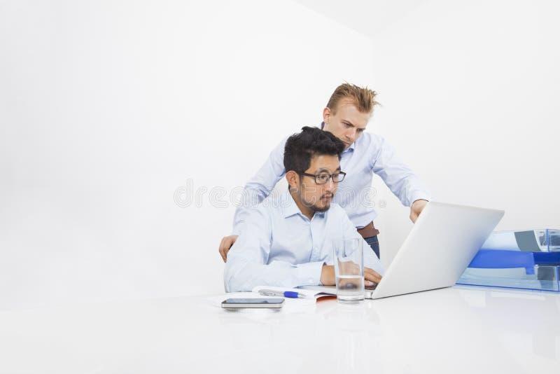 Wieloetniczni biznesmeni pracuje na laptopie przy biurkiem w biurze zdjęcie stock