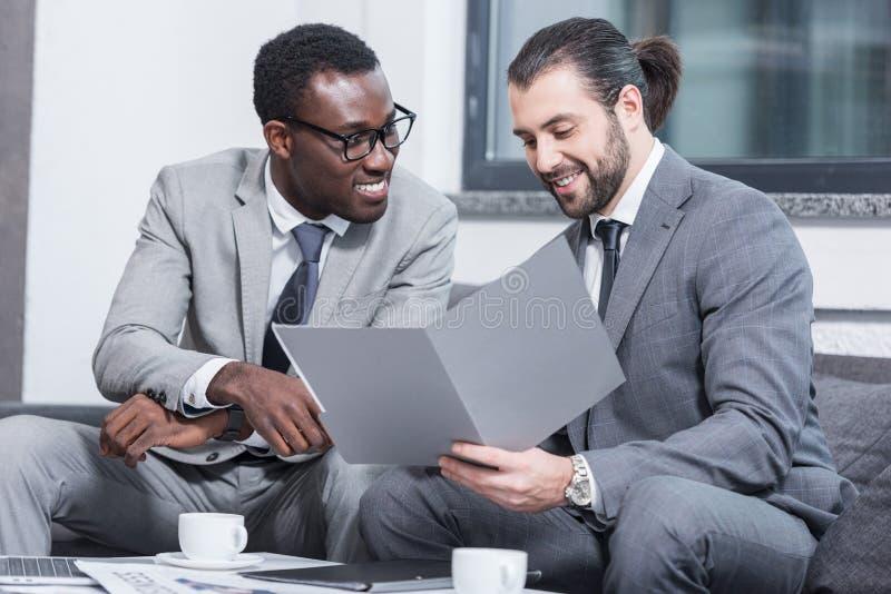 wieloetniczni biznesmeni uśmiecha się dokument i czyta zdjęcie stock