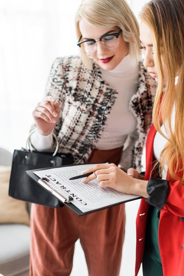 wieloetniczni bizneswomany pracuje z kontraktem na schowku w nowożytnym zdjęcia stock