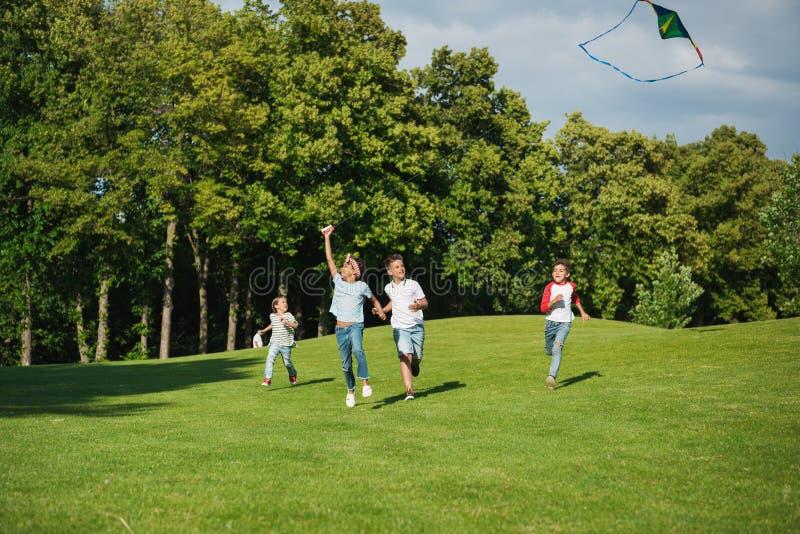 Wieloetniczni dzieciaki bawić się wpólnie podczas gdy biegający z kanią w parku zdjęcia royalty free