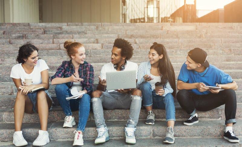 Wieloetniczni nastoletni przyjaciele komunikuje outdoors, wieczór światło słoneczne zdjęcie stock