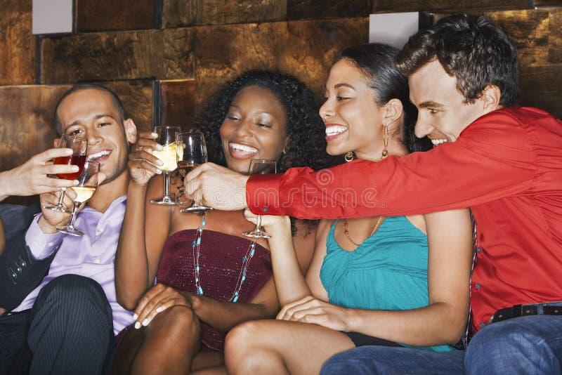 Wieloetniczni przyjaciele Wznosi toast napoje W barze obraz royalty free