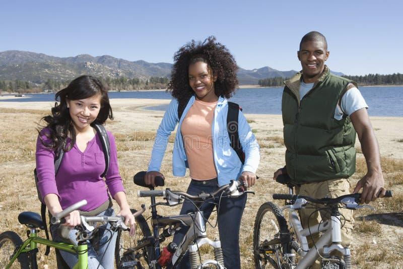Wieloetniczni przyjaciele Z rowerami górskimi jeziorem zdjęcia royalty free