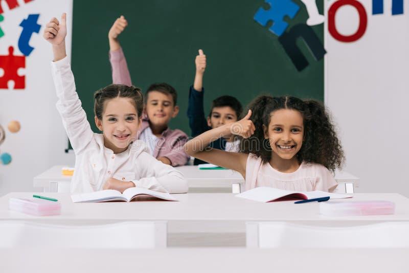 Wieloetniczni schoolkids pokazuje aprobaty w sala lekcyjnej podczas gdy siedzący przy biurkami obraz stock