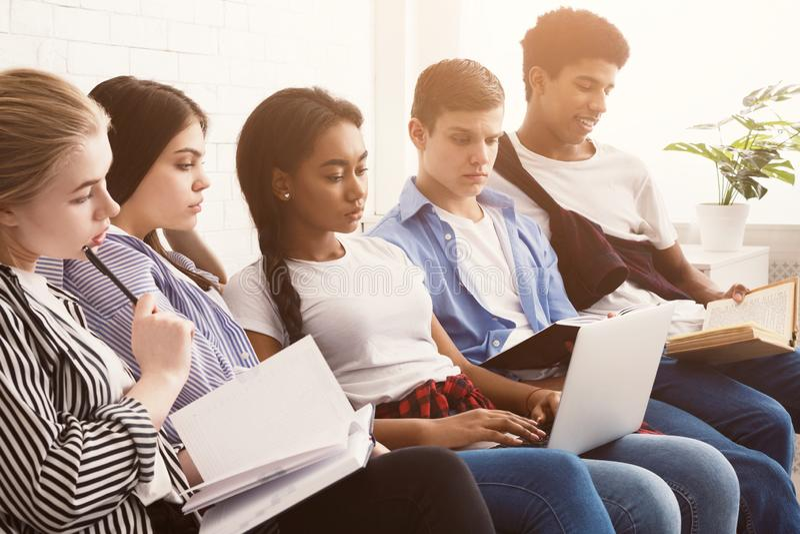 Wieloetniczni ucznie przygotowywa dla egzaminów z laptopem i książkami zdjęcia stock