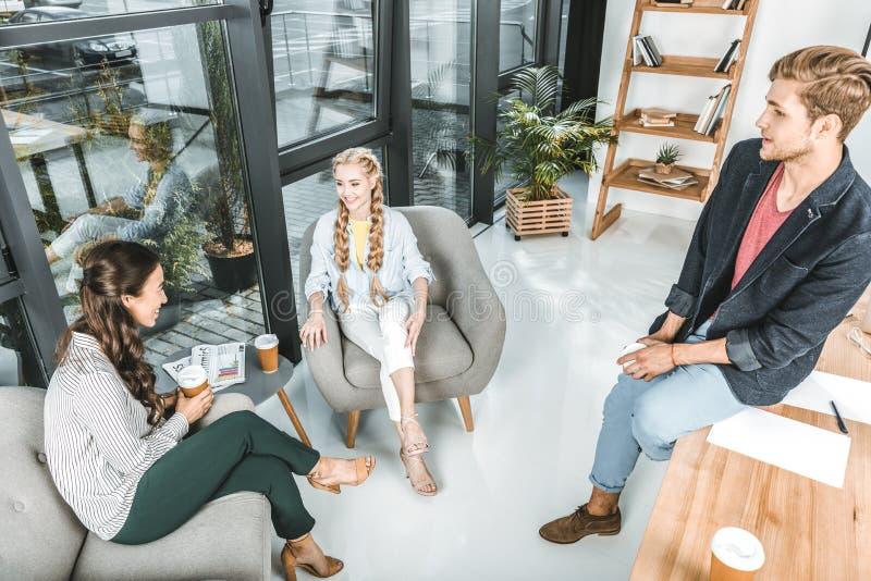 wieloetniczny biznesmen i bizneswomany odpoczywa podczas gdy mieć kawową przerwę obraz stock