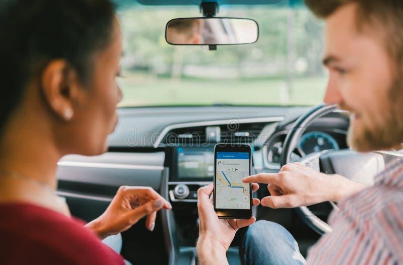 Wieloetniczny kochanek pary use system nawigacji na smartphone w samochodzie Telefonu komórkowego zastosowanie lub nowożytny gadż zdjęcie royalty free