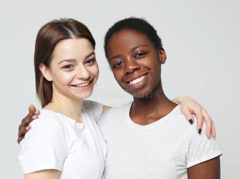 Wieloetniczny przyjaźni pojęcie Rozochocone Europejskie i Afrykańskie kobiety zdjęcie stock