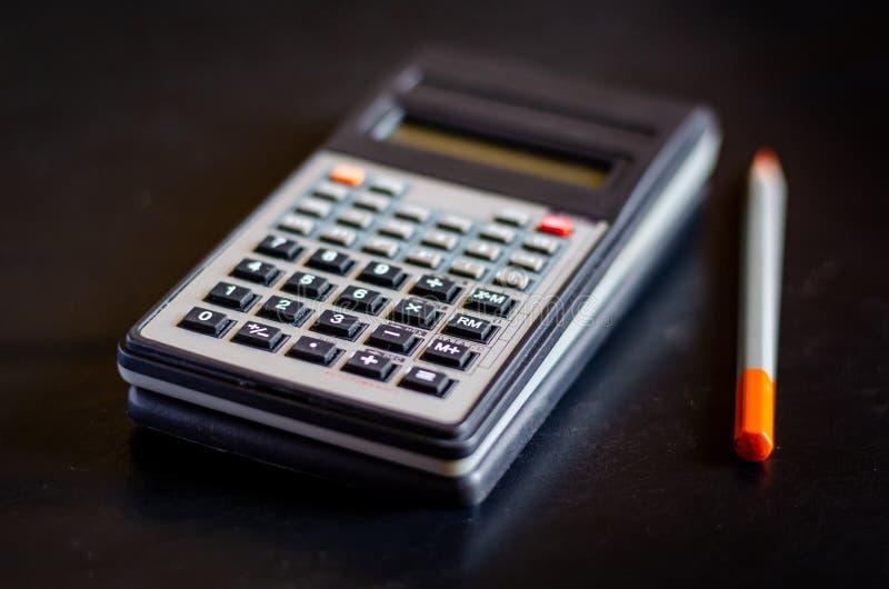 Wielofunkcyjny inżynieria kalkulator z ołówkiem na ciemnym biurku Makro- mi?kkie ogniska, obrazy royalty free