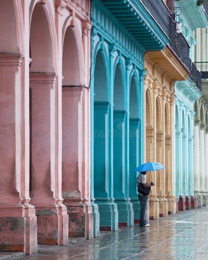 Wielokolorowe budynki główna ulica Havana Cuba z mężczyzną w deszczu z parasolem obrazy stock