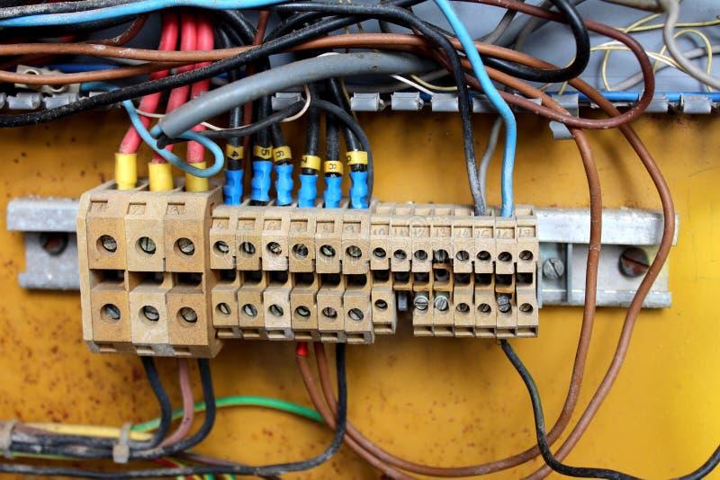 Wielokrotność brudni izolujący druty wśrodku elektrycznego pudełka łączyli z ceramicznymi elektrycznymi śmiertelnie włączników pa fotografia stock