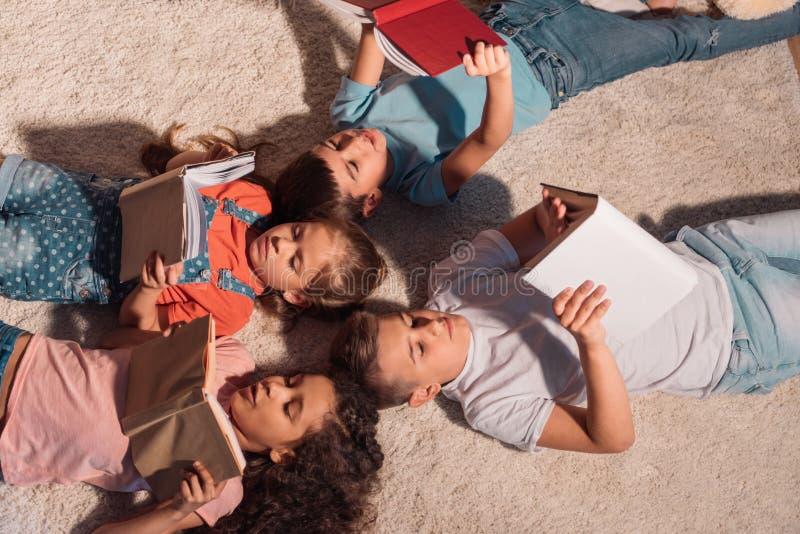 Wielokulturowa grupa dzieci kłama na podłogowych i czytelniczych książkach zdjęcia royalty free