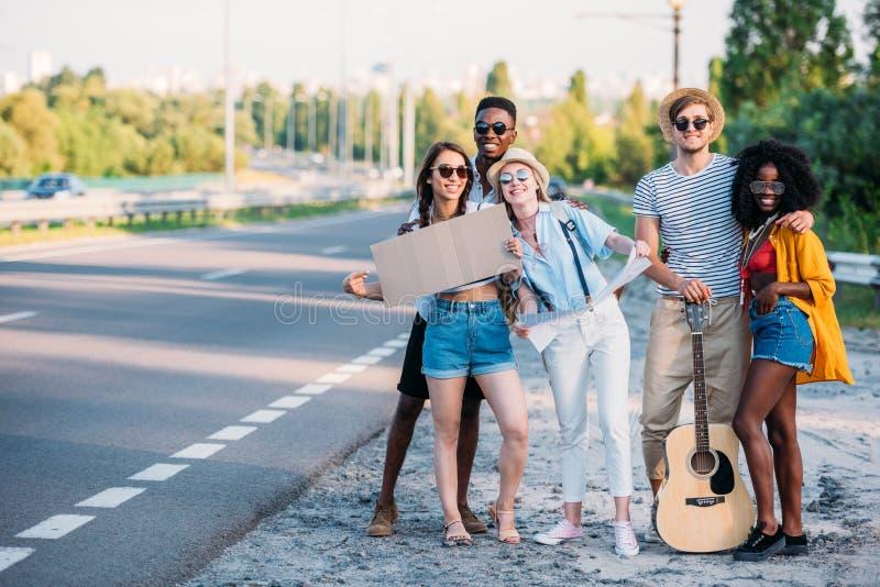 wielokulturowa grupa młodzi autostopowicze z mapą i pusta kartonowa pozycja przy chodniczkiem fotografia stock